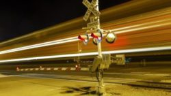 Image: A train passes a railroad crossing at night; Copyright: panthermedia.net/Joerg Hackemann
