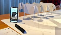 A table with paper folded elephants and a smartphone on it; copyright: Wildhood Foundation